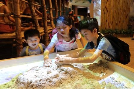 十三行博物館「八里時光機常設展」的AR擴增實境地貌沙箱有60公斤的動力砂,可同時容納至少12位小朋友一同玩耍。